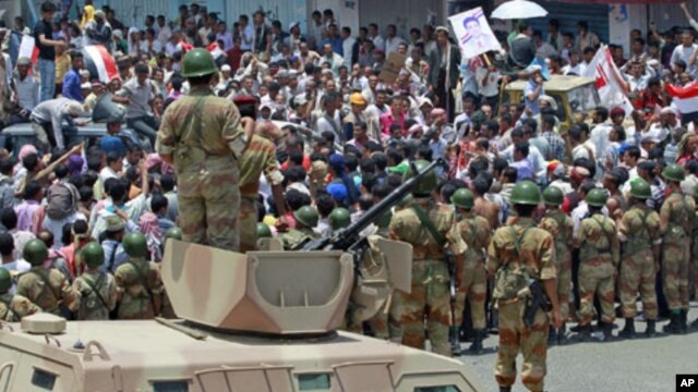 Army soldiers stand on top of armored vehicles as they block anti-government protesters at a barricade during a demonstration demanding the ouster of Yemen's President Ali Abdullah Saleh in the southern city of Taiz, April 11, 2011