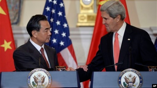 John Kerry and Wang Yi shake hands after making statements before their meeting. Sept. 19, 2013.