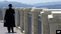 An ultra-Orthodox Jewish man walks in Ramat Shlomo, a religious Jewish settlement in an area of the West Bank annexed to Jerusalem by Israel. Israel's interior minister has given final approval for a plan to build 1,600 settler homes in the East Jerusalem