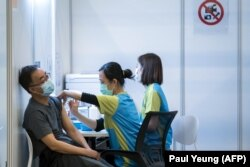 Seorang pria menerima suntikan vaksin COVID-19 buatan perusahaan farmasi China, Sinovac, di sebuah pusat vaksinasi di Hong Kong, 23 Februari 2021. (Foto: Paul Yeung/AFP)