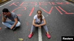 "Opposition supporters sit next to graffiti on a street that reads ""Civil resistance"" during a protest against Venezuelan President Nicolas Maduro, in Caracas, Venezuela, May 2, 2017."