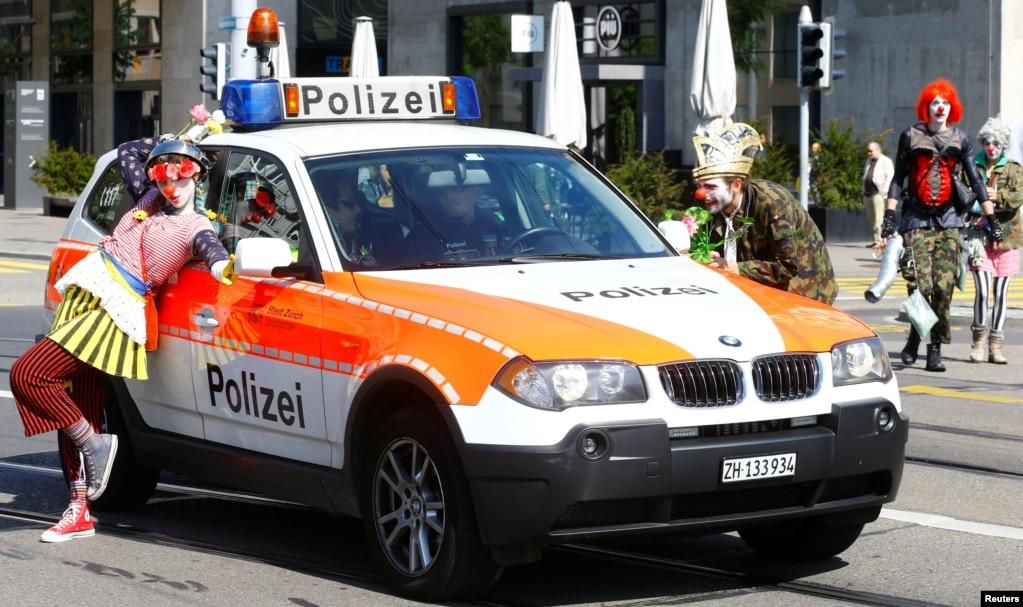 Протестующие, одетые как клоуны, позируют рядом со швейцарской полицейской машиной во время первомайской демонстрации в Цюрихе, Швейцария, 1 мая 2019 года.