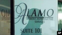 Sjenka radnika obezbjeđenja na ulaznim vratima u Alamo servis za žensku reprodukciju, 7. oktobar 2021, u San Antoniju, Teksas.