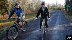 Perawat pasien Ebola yang dikarantina, Kaci Hickox (kanan) dan kekasihnya, Ted Wilbur bersepeda di dekat rumah mereka di Fort Kent, Maine (30/10).