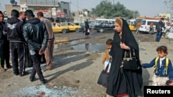 A woman with her children walks past at the site of a suicide bombing attack in the Shi'ite neighborhood of Kadhimiya in Baghdad, Iraq, Feb. 9, 2015.