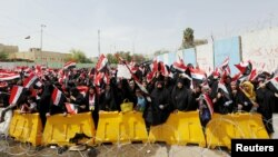 FILE - Followers of Iraq's Shi'ite cleric Muqtada al-Sadr wave Iraqi flags during a protest demanding that parliament approve a long-delayed new cabinet, in Baghdad, Iraq, April 26, 2016. The protests have since subsided.