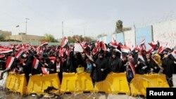 Para pengikut ulama Syiah Moqtada al-Sadr melambaikan bendera Irak dalam aksi protes di Baghdad, Irak, 26 April 2016 (Foto: dok).
