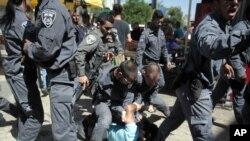 Polisi Israel menahan pria Palestina saat anak-anak muda Israel berpawai memperingati Hari Yerusalem (17/5). (AP/Mahmoud Illean)