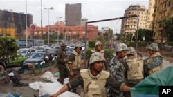 ທະຫານອິຈິບເລີກຕູບຜ້າໃບ ຂອງພວກປະທ້ວງທີ່ຈະຕຸລັດ Tahrir ໃນນະຄອນຫລວງໄຄໂຣ, ວັນທີ 13 ກຸມພາ 2011.
