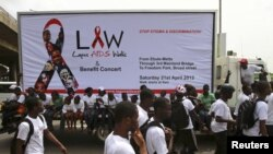 Campaigners walk through a road during a charity walk on HIV/AIDS at Ebute Mata district in Nigeria's commercial capital Lagos, April 21, 2012.