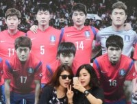 Two women take a selfie with a poster of the Korean national football team.