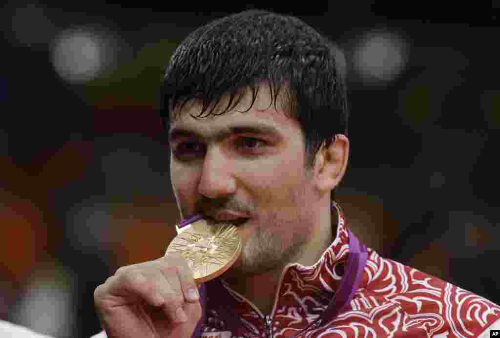 Tagir Khaibulaev, of Russia, bites his gold medal after the men's 100-kg judo competition at the 2012 Summer Olympics, Aug. 2, 2012, in London.