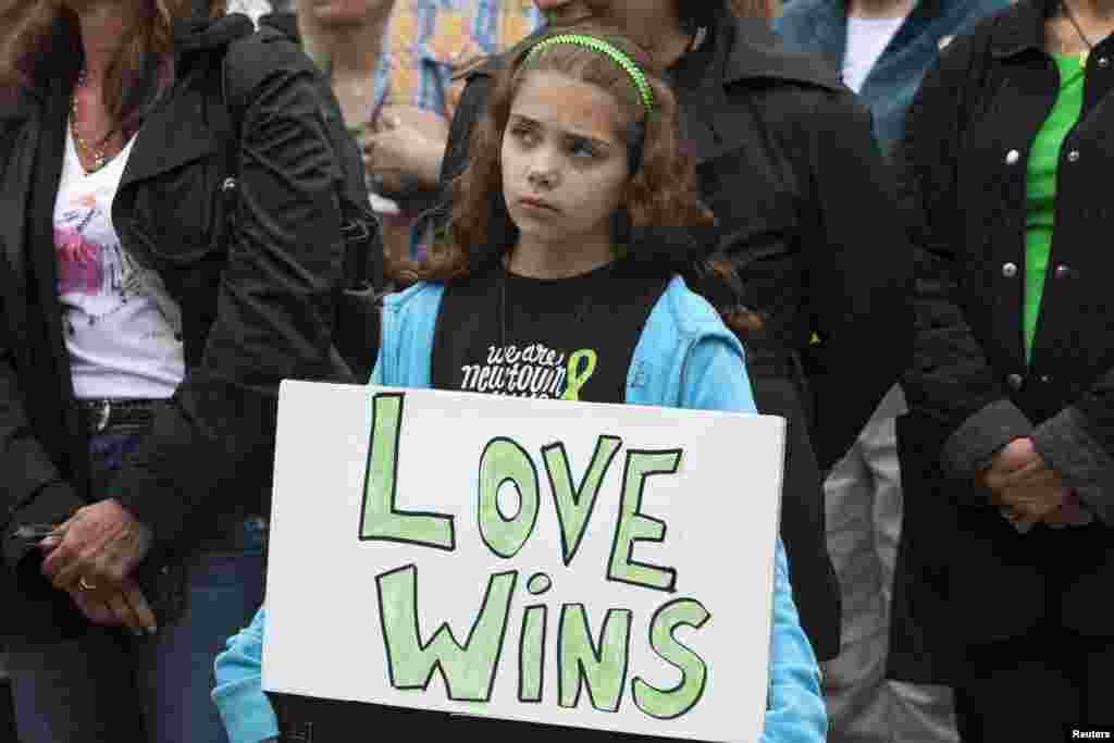A young resident holds a placard while observing the six-month anniversary of the Newtown massacre outside the town hall in Newtown, Connecticut.
