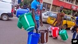 6일 서아프리카 라이베리아 몬로비아 거리에서 행상들이 물통을 팔고 있다. 보건 당국이 에볼라 감염을 막기 위해 소독약을 푼 물에 손을 자주 씻도록 권장하면서, 소독약을 풀 때 쓰는 물통 가격이 올랐다.