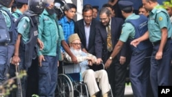 In this January 11, 2012 photo, Bangladeshi police officers escort Bangladesh's largest Islamic party Jamaat-e-Islami former chief Ghulam Azam, on wheel chair, to jail in Dhaka, Bangladesh.