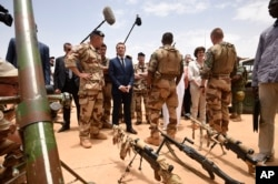 French President Emmanuel Macron, center left, visits soldiers of Operation Barkhane in Gao, Northern Mali, Friday, May 19, 2017.