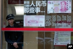 A security guard looks out near a display showing the security features of the new 100 Yuan note in Beijing, China, Jan. 7, 2016.