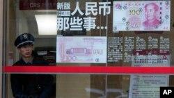 在北京,一位保安人员往外张望,他旁边有关于人民币百元新钞的介绍(2016年1月7日)