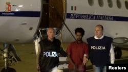 Medhanie Yehdego Mered au centre, 35 ans, est entouré par deux policiers italiens à l'aéroport de Palerme, Italie, après son arrestation à Khartoum, Soudan, le 24 mai 2016.