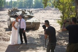 Noga and Moshiko Siho pose for wedding photos in an Israeli army staging area on the border near Kibbutz Yad Mordechai, Aug. 27, 2014.