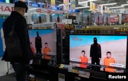 FILE - A man watches a news program about an Islamic State video purporting to show two Japanese captives at an electronics store in Tokyo, January 20, 2015.