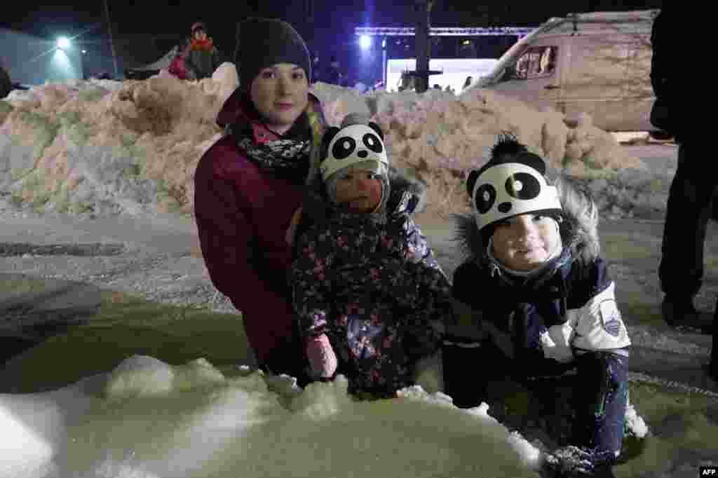 在芬兰市镇艾赫泰里举办的一场嘉年华狂欢会上,儿童戴着熊猫帽子,欢迎两只大熊猫(2018年1月18日)。