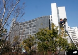 FILE - A cameraman on a ladder stands by outside Tokyo Detention Center, where former Nissan chairman Carlos Ghosn and former another executive Greg Kelly are being detained, in Tokyo, Dec. 21, 2018.