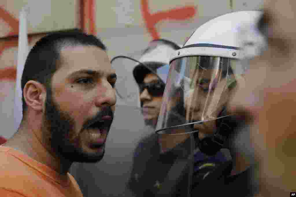 A member of the Communist-affiliated PAME labor union shouts slogans at the police during an anti-austerity protest outside of central Athens, July 3, 2015.