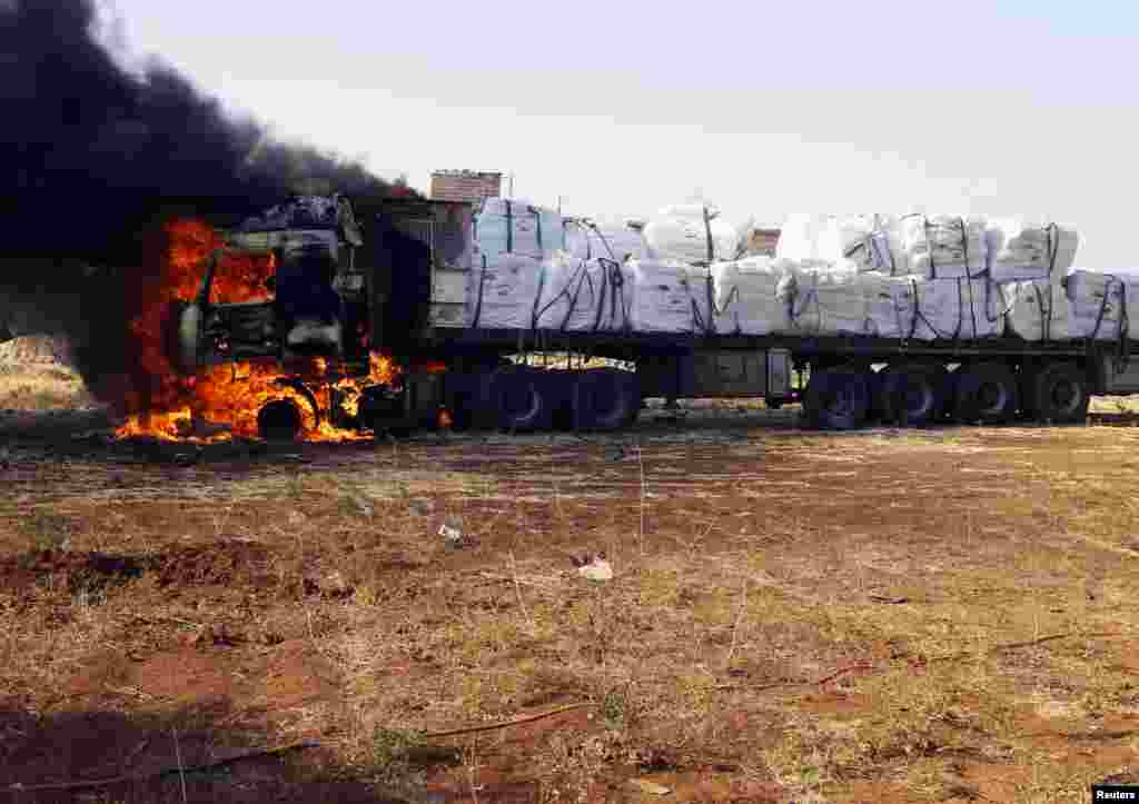 A truck catches flames after it was hit by rockets fired by a Syrian Air Force fighter plane during an air strike in the village of Tel Rafat, some 37 km (23 miles) north of Aleppo, August 9, 2012.