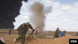 Opositores libios corren a protegerse tras la explosión durante los enfrentamientos en Ras Lanuf este miércoles 9 de marzo de 2011
