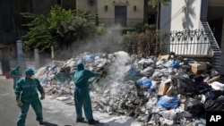 Waste management workers cover a pile of garbage using white pesticide in the Palestinian refugee camp of Sabra in Beirut, Lebanon, July 24, 2015.