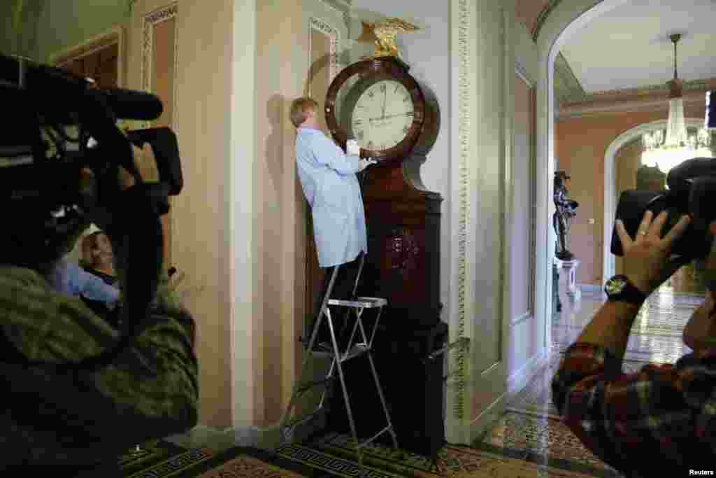 Richard Doerner, a museum specialist for the U.S. Senate, restarts the historic Ohio Clock outside the Senate floor at the U.S. Capitol in Washington, D.C. The clock had stopped during the sixteen-day government shutdown, when the staff members who wind it were furloughed as non-essential staff.