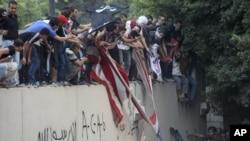 Des manifestants escaladant le mur de l'ambassade américaine au Caire