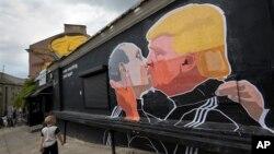 Một đứa trẻ đi qua một tranh phun sơn vẽ ứng viên tổng thống Mỹ Donald Trump ôm hôn Tổng thống Nga Vladimir Putin trên bước tường một khu phố cổ ở Vilnius, Lithuania, tháng 5/2016. (AP Photo / Mindaugas Kulbis)