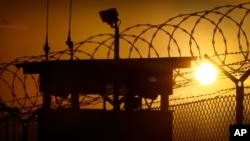 FILE - The sun rises above Camp Delta at Guantanamo Bay Naval Base, Cuba.