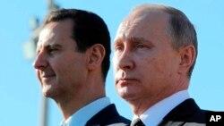 Tổng thống Nga Vladimir Putin, phải, và Tổng thống Syria Bashar Assad tại căn cứ không quân Hemeimeem ở Syria hôm 11/12. Nga bị các nhóm phiến quân ở Syria cáo buộc có âm mưu phá hỏng đàm phán hòa bình do LHQ điều giải. (Sputnik, Kremlin Pool Photo via AP)