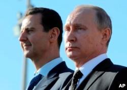 FILE - Russian President Vladimir Putin, right, and Syrian President Bashar al-Assad watch troops marching at the Hemeimeem air base in Syria, Dec. 11, 2017.