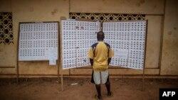 Un électeur gabonais consulte les listes d'électeurs devant un bureau de vote dans le quartier de Rio, à Libreville, 27 août 2016.