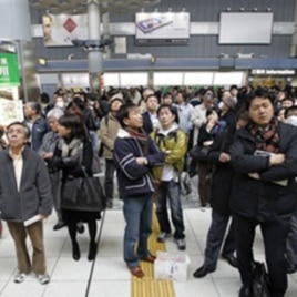Train passengers wait at Tokyo's Shinagawa station after service was halted