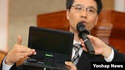 지난달 22일 북한전략센터가 주최로 서울에서 열린 '사회주의 체제전환과 미디어의 역할' 세미나에서 동아대학교 강동완 교수가 중국산 '노트텔'(EVD 플레이어)을 들고 '2013년 북한주민의 미디어 수용 실태와 과제' 주제 발표를 하고 있다. (자료사진)