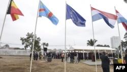Quelques personnes devant les drapeaux de la Belgique, de la RDC, de l'Union européenne à l'inauguration du chantier de construction de la nouvelle ambassade belge, 12 août 2013.