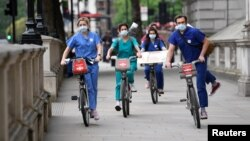 Nurses wearing face masks and riding bicycles arrive outside of Downing Street to demonstrate in a protest organised by Nurses United over pay and conditions, following the outbreak of the coronavirus disease (COVID-19), London, Britain, June 3, 2020.