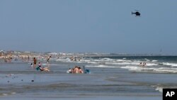 A helicopter flies close to the water as vacationers relax on the beach in Oak Island, North Carolina, June 15, 2015.