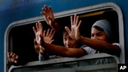 Asylum-seekers wave out of a train window as their train departs for the Hungarian border with Austria in Budapest, Hungary, Sept. 6, 2015.