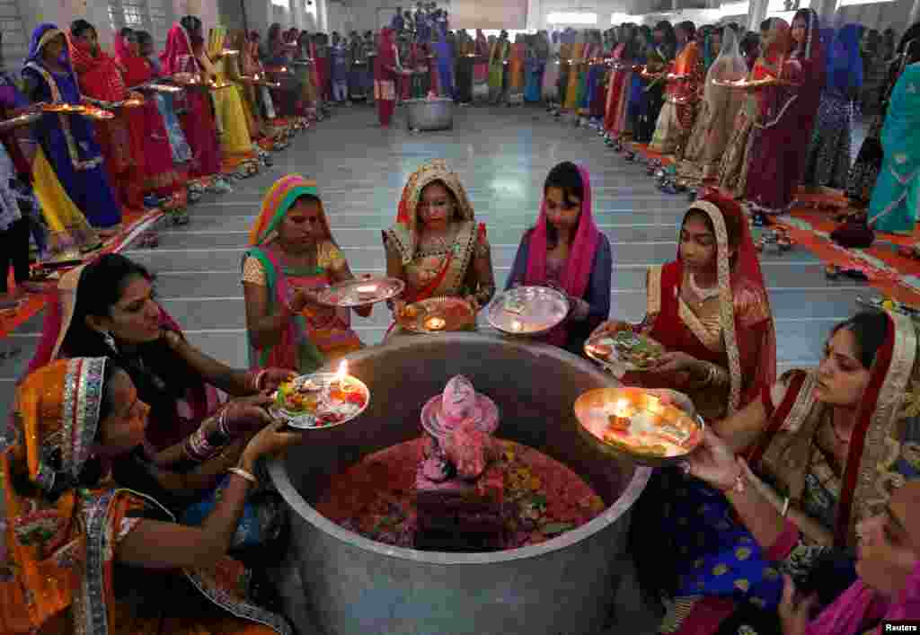 Hindu women perform a ritual known as Aarti around a Shivling (a symbol of Lord Shiva) on the last day of Jaya Parvati Vrat festival in Ahmedabad, India.