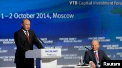 "Russia's President Vladimir Putin (L) speaks during the VTB Capital ""Russia Calling!"" Investment Forum in Moscow, Oct. 2, 2014."