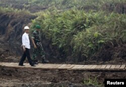 FILE - Indonesian President Joko Widodo (L) inspects a canal in Pulang Pisau, Central Kalimantan, Oct. 31, 2015. Widodo's administration is seen by many indigenous people as dragging its feet on the return of forest land to indigenous people.