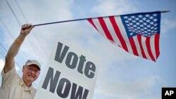 3月13号,阿拉巴马州一位选民在投票站外面向过路的车辆挥舞国旗