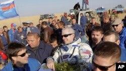 El astronauta estadounidense Steve Swanson es cargado por especialistas a su aterrizaje en Kazakstan.