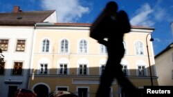FILE - A person passes the house in which Nazi dictator Adolf Hitler was born in Braunau am Inn, Austria, Sept. 24, 2012.